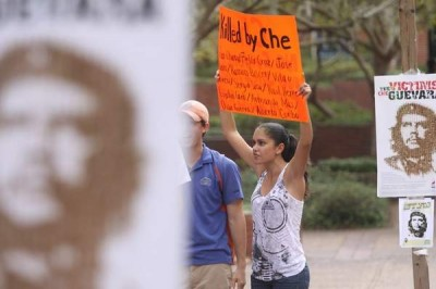 "As another birthday of Ernesto ""Che"" Guevara passes, University of Florida political science major Dayme Sanche, 20, holds a sign that says ""Killed by Che"" Friday on Turlington Plaza. Zachary Bennett/The Gainesville Sun"