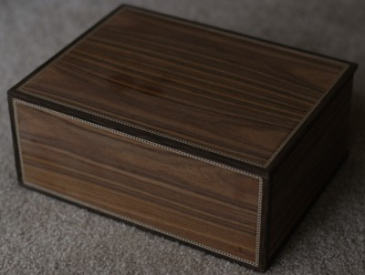 The humidor is constructed of Honduran mahogany with a rosewood veneer. Wenge edging and maple stringing provide the accents on the corners and edges.