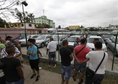 People line up to buy used cars at a government owned dealership in Havana