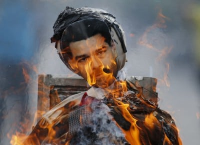 Anti-government protesters burn an effigy depicting Venezuela's President Nicolas Maduro in Caracas