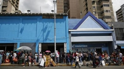 "Venezuelans at a  ""cola"" (queuing or waiting in line) at a pharmacy"