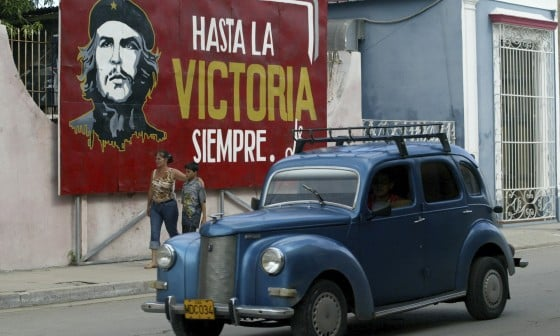 A vintage car passes a Che Guevara mural in Cuba