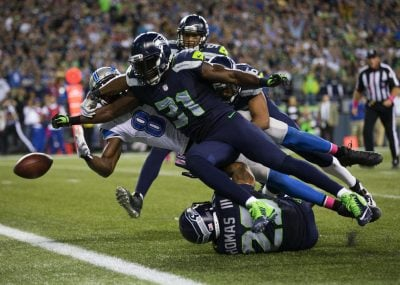 Seahawks safety Kam Chancellor hits the ball free from Lions wide receiver Calvin Johnson punching it through the end zone for a touchback in the fourth quarter during Monday Night Football at CenturyLink Field, Oct. 5, 2015.  (Dean Rutz / The Seattle Times)