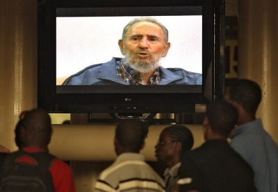 People watch retired Cuban leader Fidel Castro during an interview on Cuban Television in Havana July 12, 2010. Castro emerged from seclusion on Monday to warn the world in a taped interview aired on national television that the West's confrontation with Iran could erupt into nuclear war. Castro has been seen only in occasional photographs and videos since he underwent emergency intestinal surgery in July 2006 and ceded power provisionally to his younger brother, Raul Castro. REUTERS/Enrique De La Osa (CUBA - Tags: POLITICS)