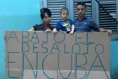 Reverend Yiorvis Bravos Denis and family holding a sign which reads 'Stop eviction in Cuba'.
