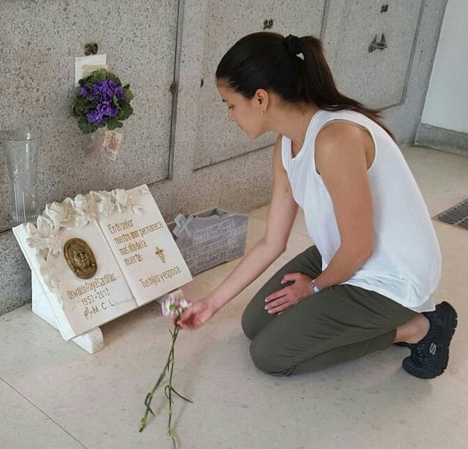 Rosa Maria Paya lays flowers at her father Oswaldo Paya's grave in Cuba.